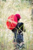 Asiatisk kvinna i trädgård med rött Arkivfoto