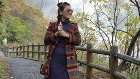 Asiatisk kvinna med att regna paraplyet som går i varm vår en för jigokudani av mest populär resande destination i sapporo hokkai lager videofilmer