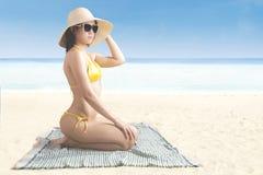 Asiatisk kvinna med baddräkten på kusten Arkivfoto