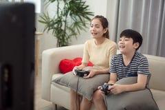 Asiatisk kvinna med den asiatiska pojken som hemma spelar videospel Arkivfoto
