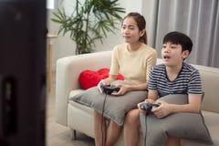 Asiatisk kvinna med den asiatiska pojken som hemma spelar videospel Royaltyfria Foton