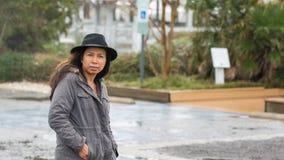 Asiatisk kvinna med den svarta hatten och anoraken som ser fotografen arkivbild