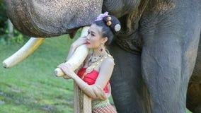 Asiatisk kvinna med elefanten i liten vik, Thailand arkivfilmer