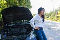 Asiatisk kvinna med en bruten bil med den öppna huven royaltyfri fotografi