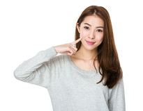 Asiatisk kvinna med fingerpunkt till henne skrattgropar Fotografering för Bildbyråer