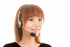 Asiatisk kvinna med hörlurar med mikrofonmikrofonen Royaltyfria Bilder