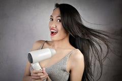 Asiatisk kvinna med haurdryer royaltyfri foto