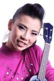 Asiatisk kvinna med ukulelet Arkivfoto