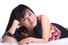 Asiatisk kvinna på säng Royaltyfria Bilder