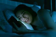 Asiatisk kvinna på säng sent på natten som smsar genom att använda mobiltelefongummihjulet arkivfoton