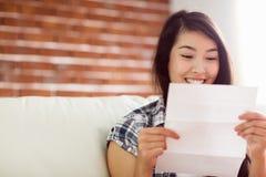 Asiatisk kvinna på soffaläsningbokstaven Arkivfoto