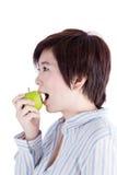 Asiatisk kvinna som äter ett grönt äpple Fotografering för Bildbyråer