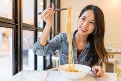 Asiatisk kvinna som äter nudlar i kinesisk restaurang Arkivbild