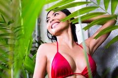 Asiatisk kvinna som använder duschen i tropisk trädgård Royaltyfri Foto
