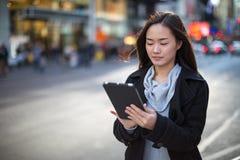 Asiatisk kvinna som använder minnestavlaPC Royaltyfri Foto