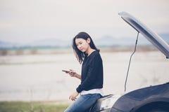 Asiatisk kvinna som använder mobiltelefonen, medan se och stressad mansi royaltyfria bilder