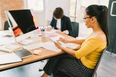Asiatisk kvinna som använder smartphonen och den skrivbords- datoren på det moderna kontoret, kollega på skrivbordsarbete i bakgr arkivbild
