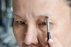 Asiatisk kvinna som applicerar makeup med ögonbrynborsten Royaltyfri Bild