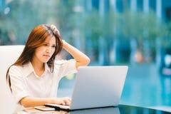 Asiatisk kvinna som arbetar med det hemmastadda eller moderna kontoret för bärbar dator Allvarligt, förvirrat eller frustrerat ut arkivfoto