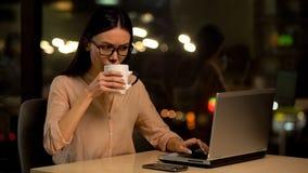 Asiatisk kvinna som arbetar p? b?rbara datorn och att dricka kaffe f?r att vara vaket och inspirerat p? natten arkivfoto