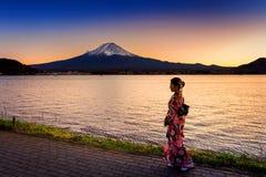 Asiatisk kvinna som bär den japanska traditionella kimonot på det Fuji berget Solnedgång på Kawaguchiko sjön i Japan Royaltyfri Bild