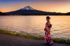 Asiatisk kvinna som bär den japanska traditionella kimonot på det Fuji berget Solnedgång på Kawaguchiko sjön i Japan Royaltyfria Bilder