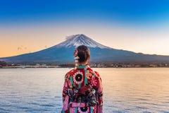 Asiatisk kvinna som bär den japanska traditionella kimonot på det Fuji berget Solnedgång på Kawaguchiko sjön i Japan Fotografering för Bildbyråer