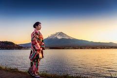 Asiatisk kvinna som bär den japanska traditionella kimonot på det Fuji berget Solnedgång på Kawaguchiko sjön i Japan arkivbild
