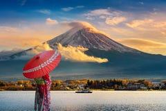 Asiatisk kvinna som bär den japanska traditionella kimonot på det Fuji berget Solnedgång på Kawaguchiko sjön i Japan arkivbilder
