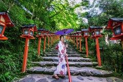 Asiatisk kvinna som bär den japanska traditionella kimonot på Kifune Shrine i Kyoto, Japan arkivbilder