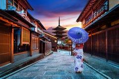 Asiatisk kvinna som bär den japanska traditionella kimonot på den Yasaka pagoden och den Sannen Zaka gatan i Kyoto, Japan royaltyfri bild