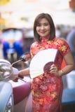 Asiatisk kvinna som bär den toothy le framsidan för kinesisk kvinnatraditionskläder i stad för yaowaratgatabangkok porslin arkivbild