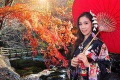 Asiatisk kvinna som bär den traditionella japanska kimonot med det röda paraplyet Arkivbild