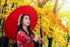 Asiatisk kvinna som bär den traditionella japanska kimonot med det röda paraplyet Arkivbilder