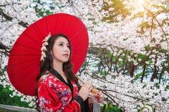 Asiatisk kvinna som bär den traditionella japanska kimonot med det röda paraplyet Arkivfoto