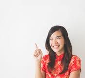 Asiatisk kvinna som bär klänningen för traditionell kines som pekar upp Royaltyfria Bilder