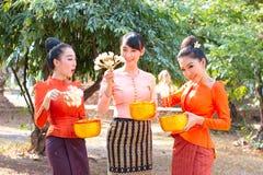 Asiatisk kvinna som bär traditionell thailändsk kultur på templet som spelar vatten i den Songkran dagen royaltyfri foto