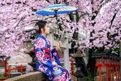 Asiatisk kvinna som b?r den japanska traditionella kimonot och den k?rsb?rsr?da blomningen i v?ren, Kyoto tempel i Japan royaltyfri fotografi