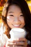 Asiatisk kvinna som dricker en varm drink royaltyfria bilder