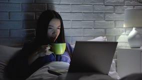 Asiatisk kvinna som dricker kaffe som sent arbetar på bärbara datorn i sovrummet som möter stopptid stock video