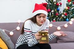 Asiatisk kvinna som förargas när öppen ask för guldxmas-gåva på feriepartiet på soffan, gåva för ledajulparti royaltyfria foton