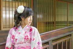Asiatisk kvinna som framme bär en yukata av fönster för japansk stil royaltyfri bild
