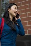 Asiatisk kvinna som går och talar på hennes telefon Arkivfoto