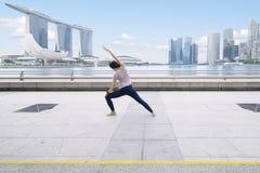 Asiatisk kvinna som gör sträckning på promenadbron Arkivbild