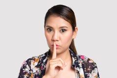 Asiatisk kvinna som gör tystnadtecknet mot Royaltyfria Foton