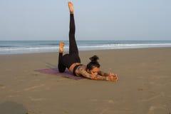 Asiatisk kvinna som gör yoga på kusterna av ett varmt hav Arkivfoto
