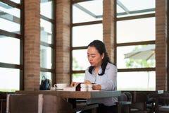 Asiatisk kvinna som har kaffe och läser i stången fotografering för bildbyråer