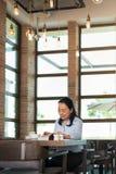 Asiatisk kvinna som har kaffe och l?ser i st?ngen royaltyfri foto