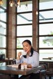 Asiatisk kvinna som har kaffe och l?ser i st?ngen royaltyfri fotografi