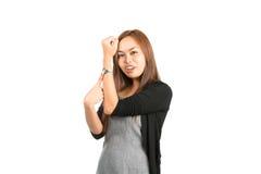 Asiatisk kvinna som indikerar Tid som pekar på klockan Arkivbild